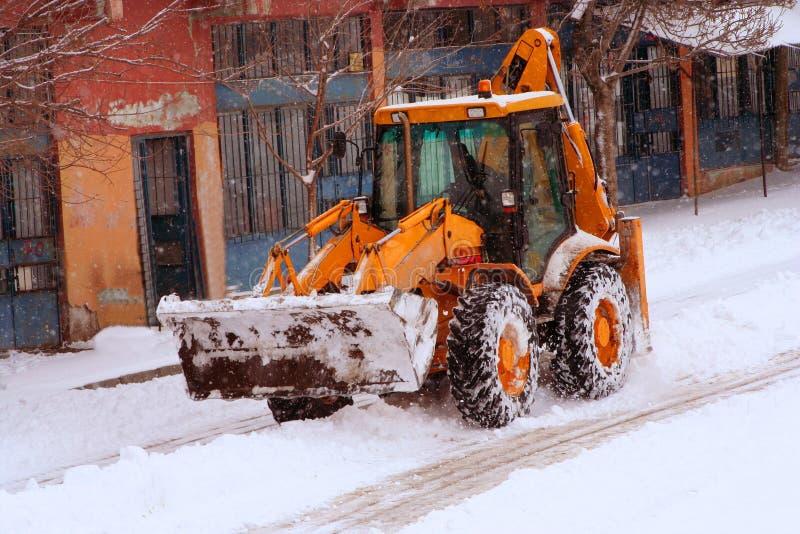 Un carro ceaning la calle mientras que nieva fotografía de archivo