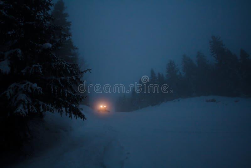 Un carro con las luces en el camino del invierno fotografía de archivo