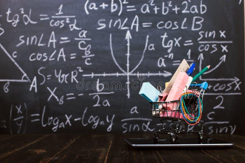 Un carro de la compra con las fuentes de escuela en la tableta, en la tabla contra la pizarra del fondo Concepto de nuevo a la pr imagen de archivo libre de regalías
