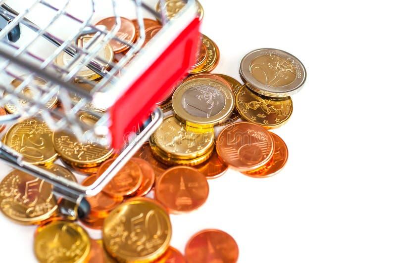 Un carro de la compra con las monedas euro fotografía de archivo libre de regalías