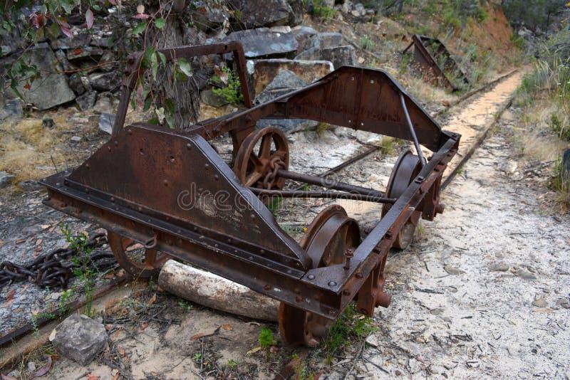 Un carro minero abandonado se sienta en las vías cerca de una mina en desuso en Australia fotos de archivo