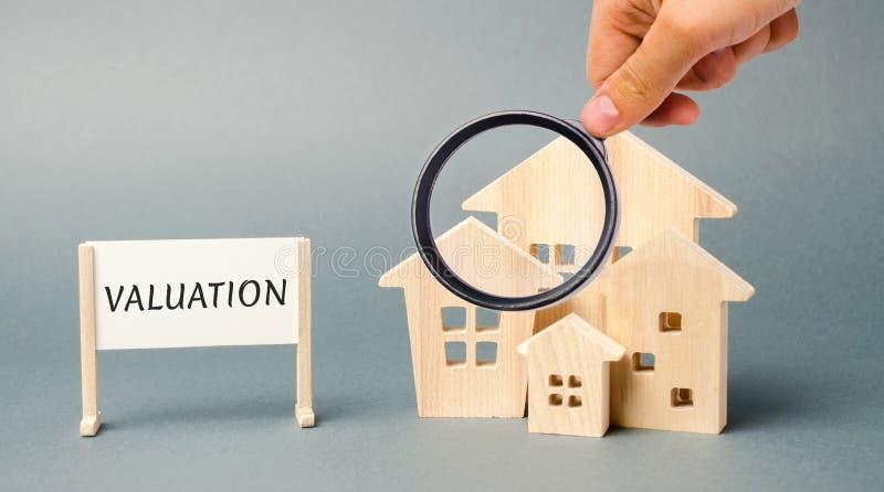 Un cartel con la evaluación de la palabra y una casa de madera miniatura Valoraci?n de Real Estate Valore la propiedad/el hogar S fotografía de archivo libre de regalías