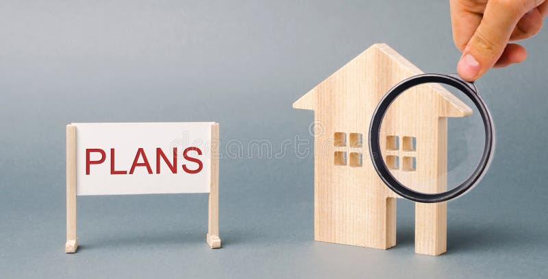 Un cartel con los planes de la palabra y una casa de madera miniatura Inversi?n de la propiedad Planeamiento de estado Vivienda d imagen de archivo