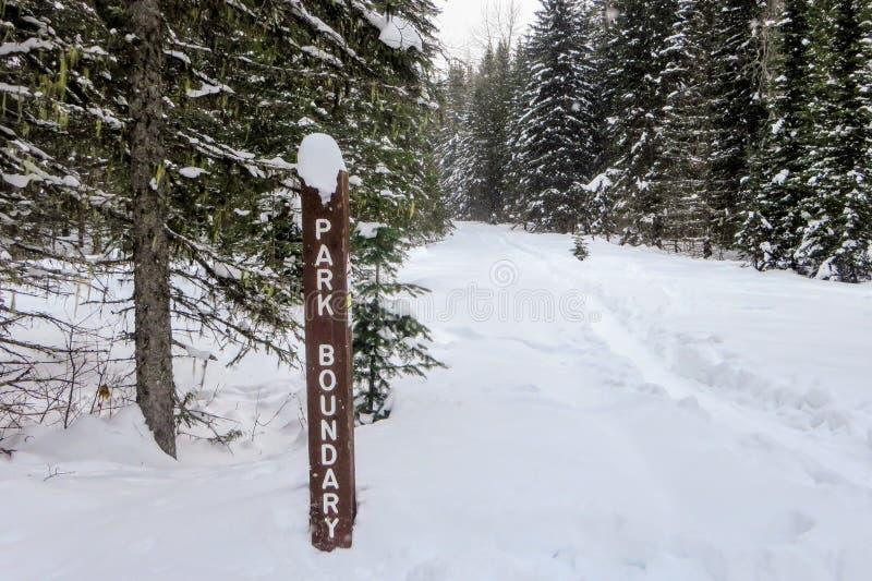 Un cartello di frontiera del parco lungo un percorso d'escursione invernale nelle foreste nevose del parco provinciale di Fernie  fotografie stock