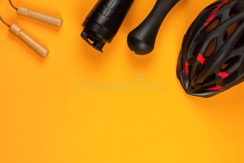 Un casque noir à côté d'une bouteille d'eau sur le fond jaune photos stock