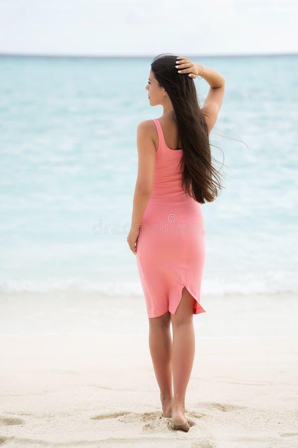 Un castana in un vestito adatto rosa sta con lei di nuovo alla macchina fotografica immagine stock libera da diritti