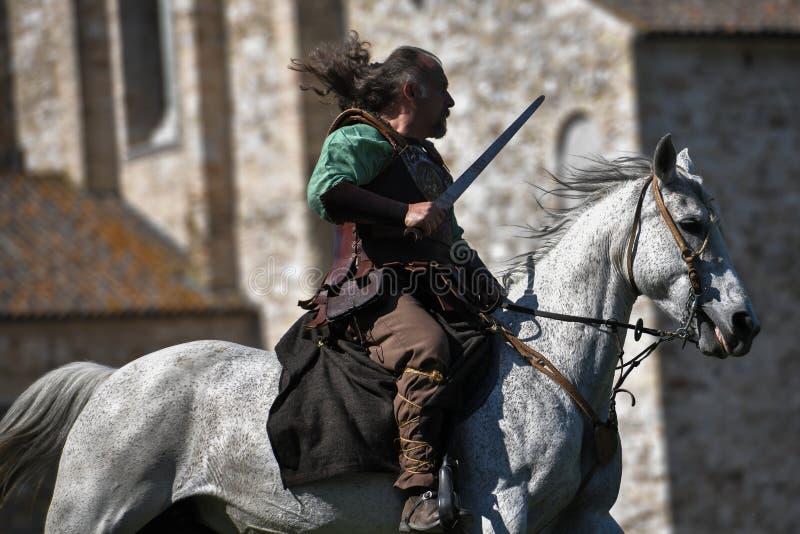 Un cavaliere celto in costume tradizionale tiene una spada e monta un cavallo fotografia stock libera da diritti