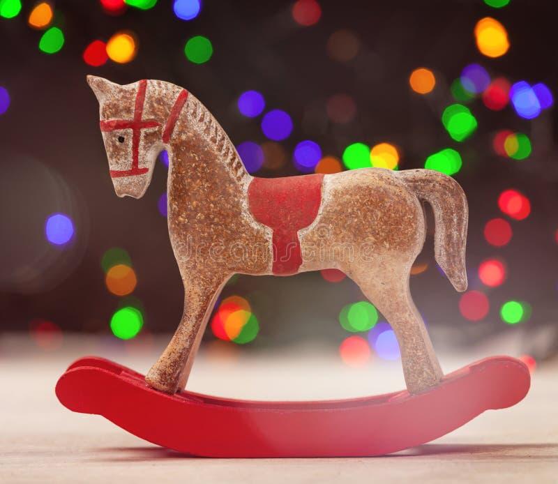 Un cavallo a dondolo con le luci di natale su fondo immagine stock