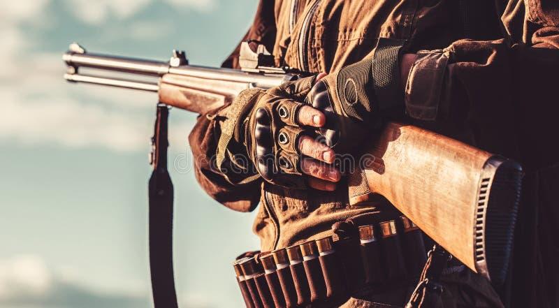 Un cazador con una forma de búsqueda del arma y de la búsqueda para cazar en un bosque del otoño el hombre está en la caza Hombre imagen de archivo