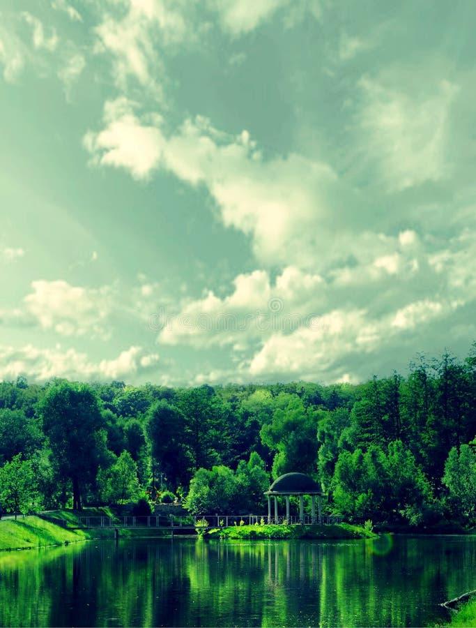 Un cenador del gazebo en el parque viejo y su reflexión en el agua contra el cielo, demasiado grande para su edad con las nubes fotografía de archivo