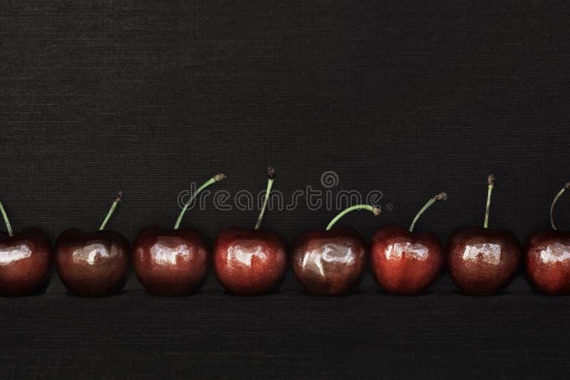 Un centro di otto varietà delle ciliege sul fondo nero del tessuto immagine stock libera da diritti