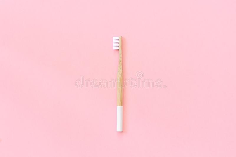 Un cepillo de bambú respetuoso del medio ambiente natural con las cerdas blancas en el fondo rosado de papel Concepto in?til cero imagen de archivo