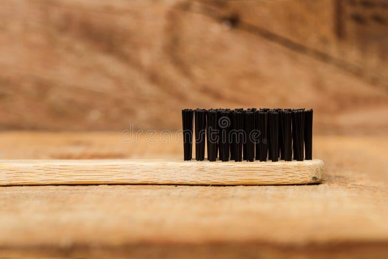 Un cepillo de dientes de bambú con las cerdas de cepillo negras foto de archivo libre de regalías