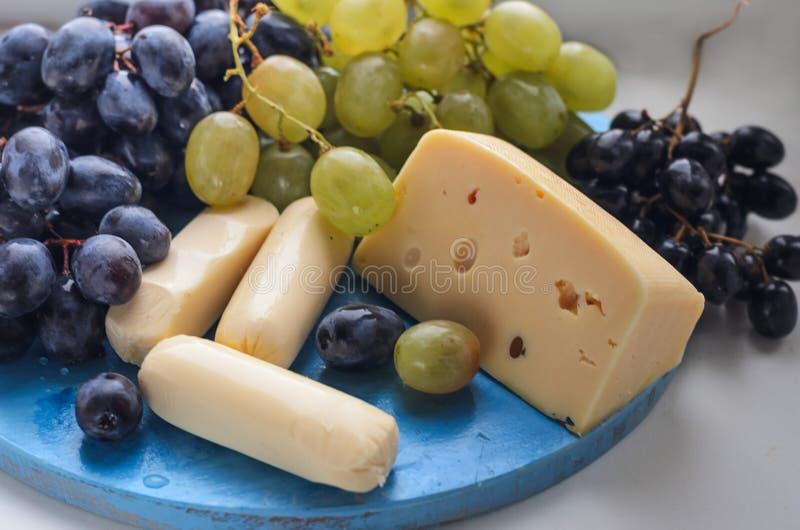 Un cepillo de uvas en una taza de madera Dos clases de queso imágenes de archivo libres de regalías