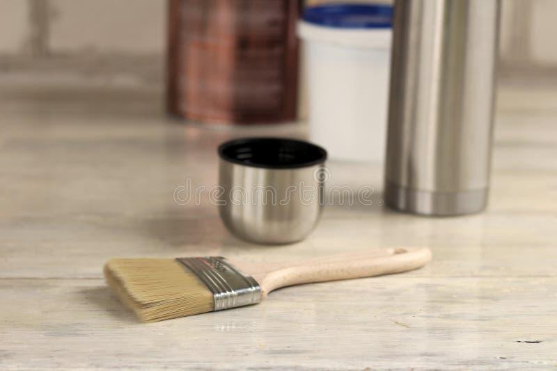 Un cepillo miente al lado de un cubo plástico de la pintura con una tapa azul, una poder del metal, un termo con una taza en un v imágenes de archivo libres de regalías