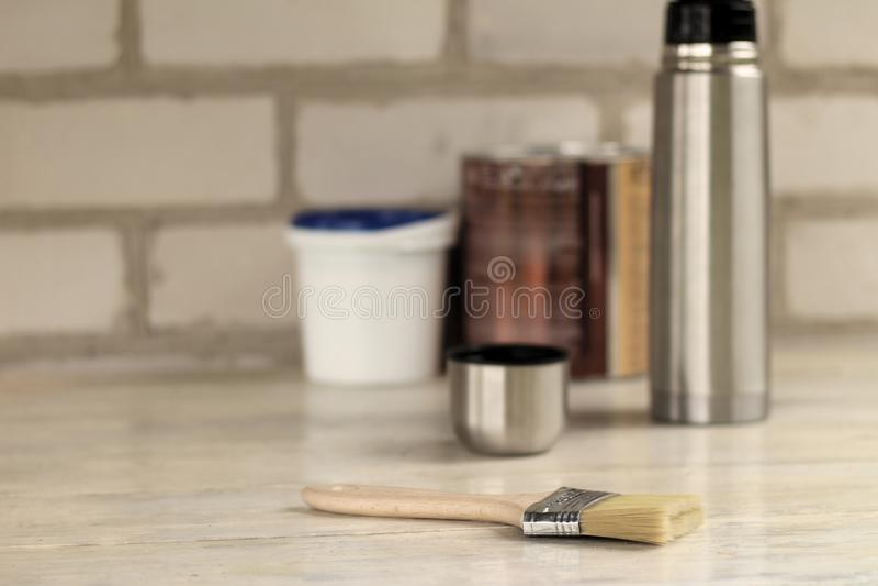 Un cepillo miente al lado de un cubo plástico de la pintura con una tapa azul, una poder del metal, un termo con una taza en un v fotos de archivo