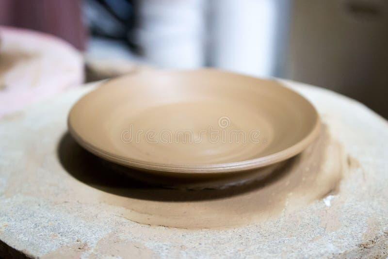Un ceramist principal avec 13 ans d'expérience a fait plusieurs plats à partir de l'argile rouge sur une roue de potier, sur une  image libre de droits