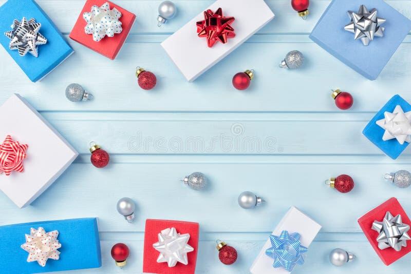In un cerchio di fondo blu sono le palle rosse e d'argento di Natale, contenitori di regalo con gli archi Composizione in Natale, immagine stock