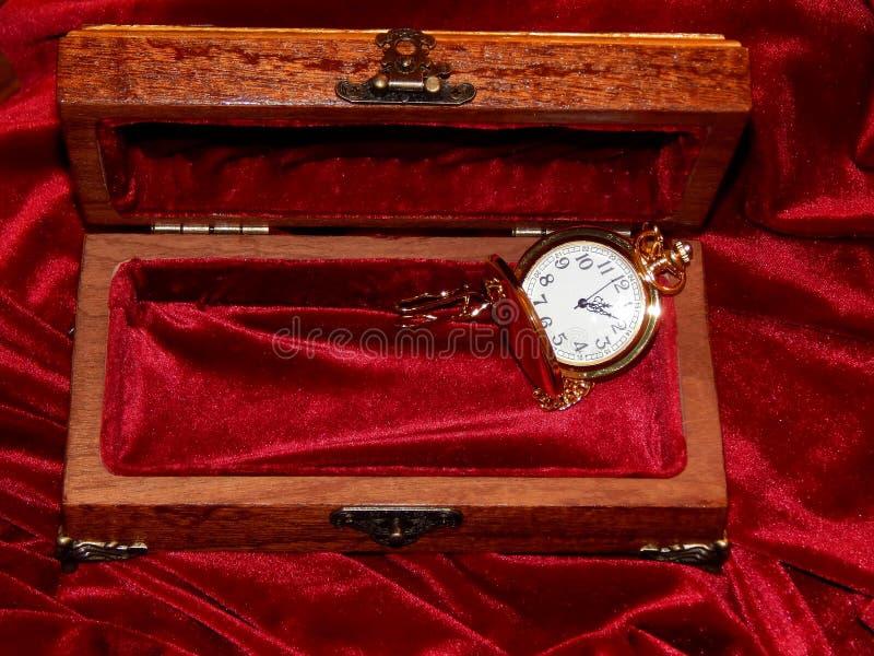 Un cercueil d'acajou fait main avec des montres et des diamants sur le velours photographie stock libre de droits