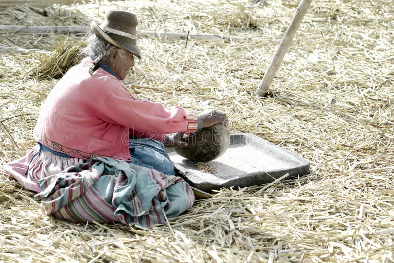 Un cereale anziano della macinazione della donna di Aymara, Uros Floating Islands, il Titicaca, Perù immagine stock libera da diritti