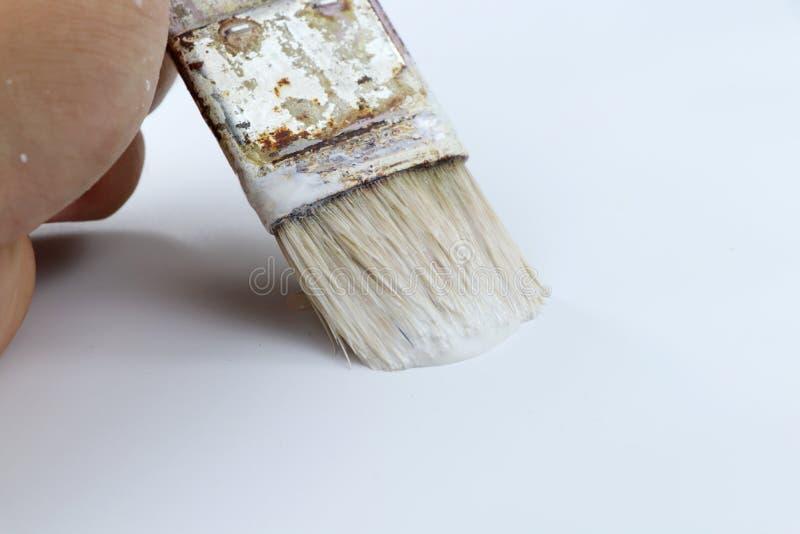 Un certain mur de peinture d'homme utilisant la couleur blanche Une vieille petite brosse pour l'exactitude images stock
