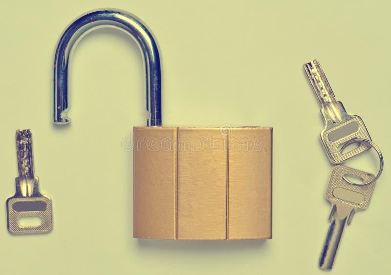 Un château doré ouvert et clés d'isolement sur le fond gris Ho image stock