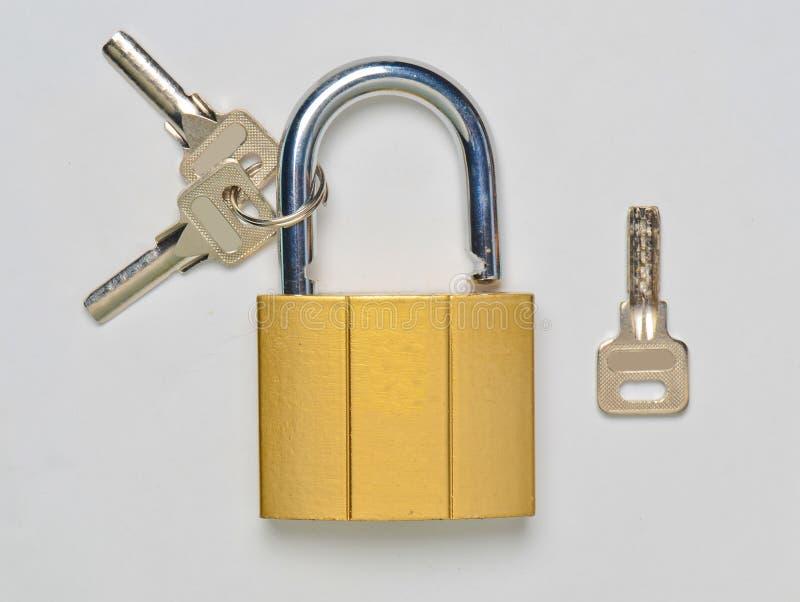 Un château doré ouvert et clés sur un fond gris Protection à la maison contre le vol photographie stock