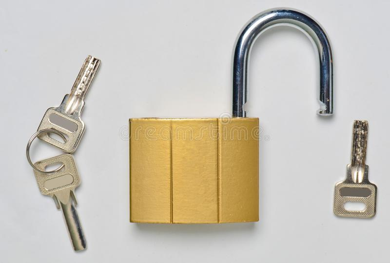 Un château doré ouvert et clés sur un fond gris Protection à la maison contre le vol photos stock