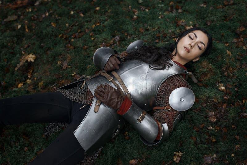 Un chainmail que lleva y una armadura de la muchacha hermosa del guerrero que mienten en la tierra en un bosque misterioso foto de archivo libre de regalías