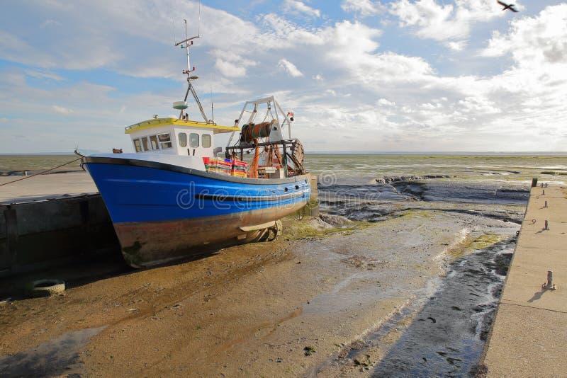Un chalutier de pêche coloré amarré au quai avec la plage boueuse à marée basse, Leigh sur la mer photo libre de droits