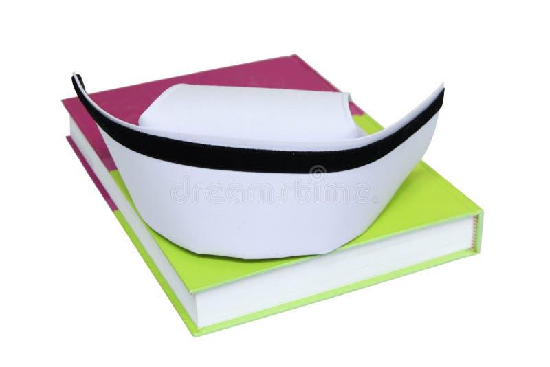 Un chapeau d'isolement d'infirmière sur le manuel photographie stock libre de droits