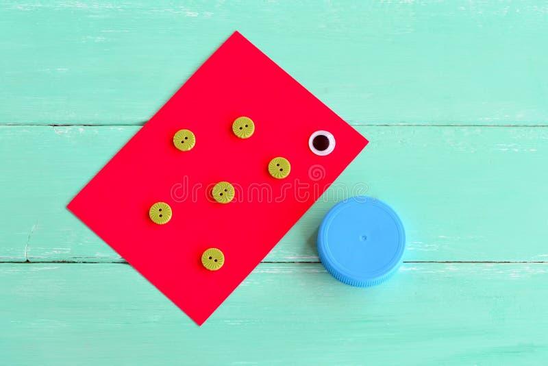 Un chapeau d'une bouteille en plastique, boutons, feuille de carton, un oeil en plastique - placez pour faire les poissons des mé images libres de droits