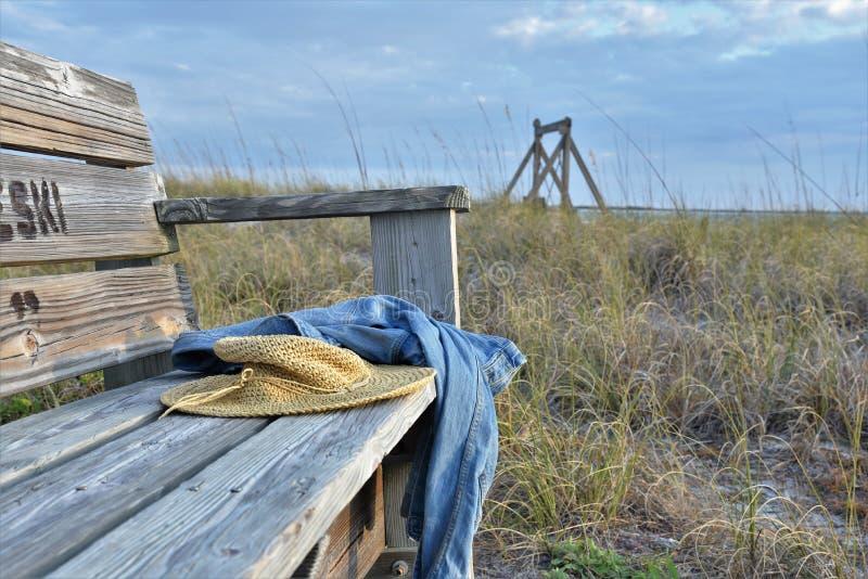 Un chapeau tissé et jeans sur un banc en bois photos stock