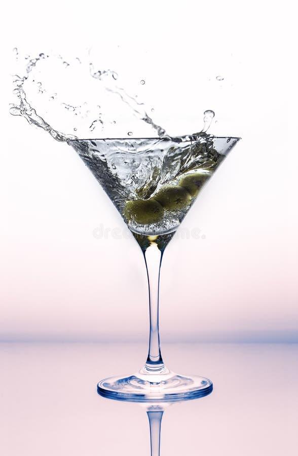 Un chapoteo de martini en un vidrio de cóctel con las aceitunas fotos de archivo libres de regalías
