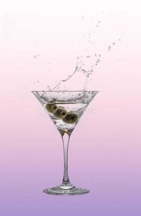 Un chapoteo de martini en un vidrio de cóctel con las aceitunas fotografía de archivo libre de regalías
