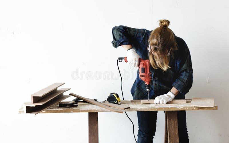 Un charpentier à l'aide d'un foret sur un bois photographie stock libre de droits