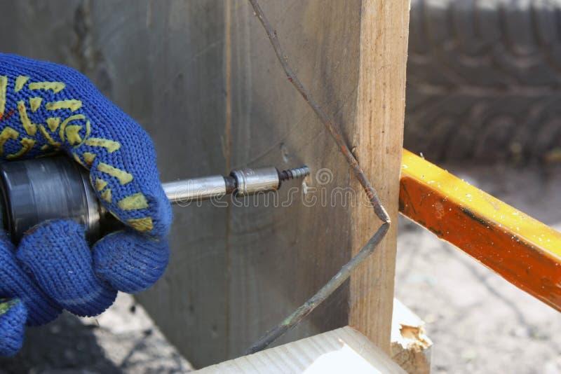 Un charpentier travaillant avec un tournevis électrique réparant une barrière en bois dans les gants protecteurs image stock