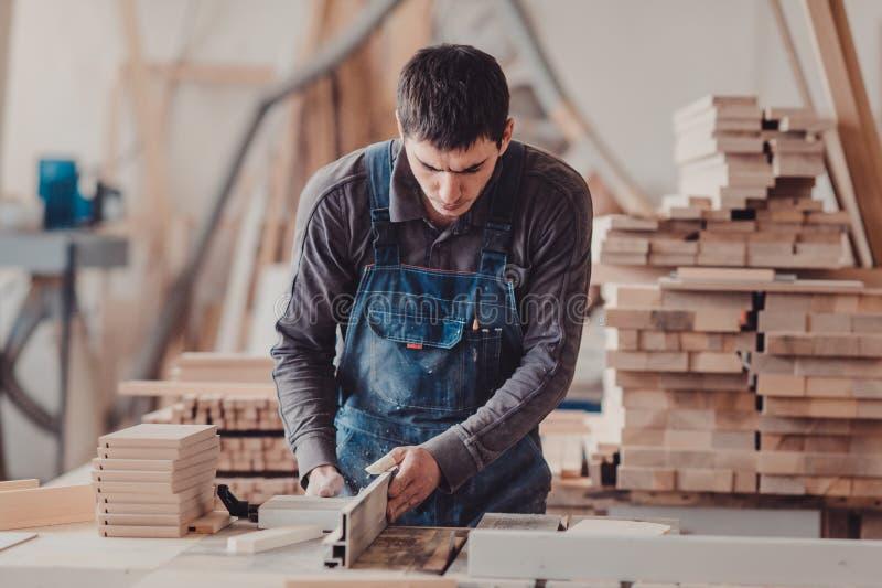 Un charpentier travaille au travail du bois la machine-outil Charpentier travaillant aux machines de travail du bois dans la bout images libres de droits
