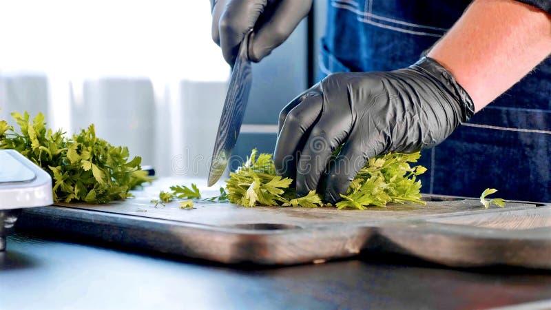 Un chef dans les gants noirs coupe le persil sur le conseil en bois photo stock