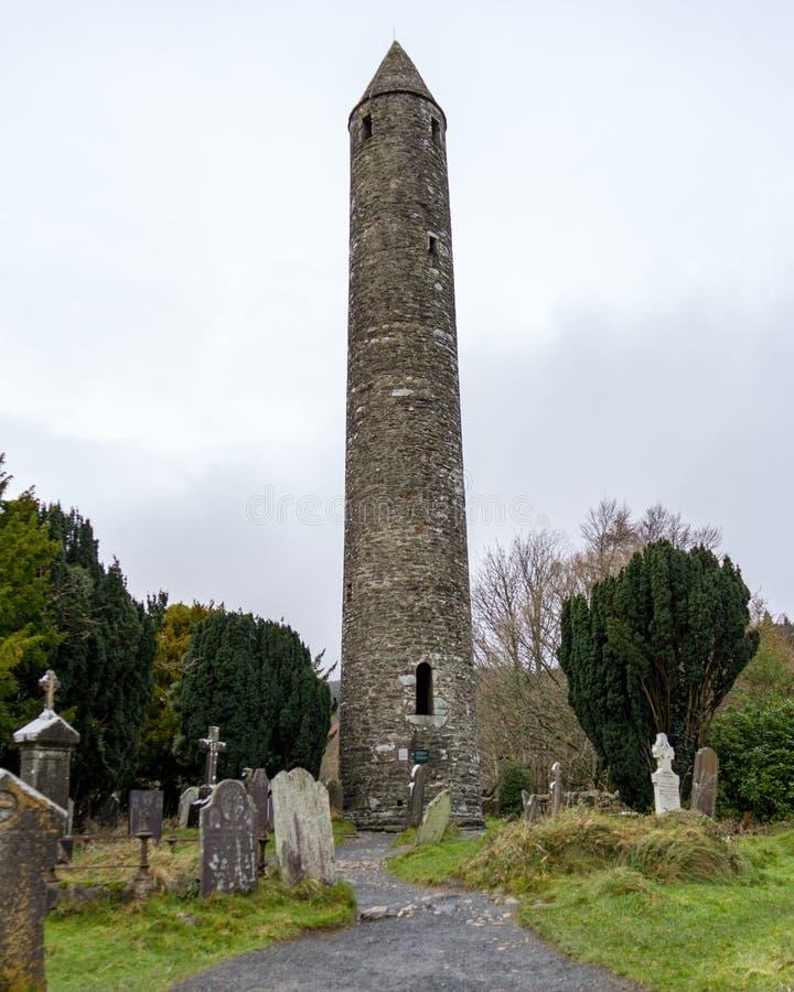 Un chemin mène par un cimetière antique à la tour ronde au site monastique de Glendalough dans Wicklow, Irlande photographie stock libre de droits
