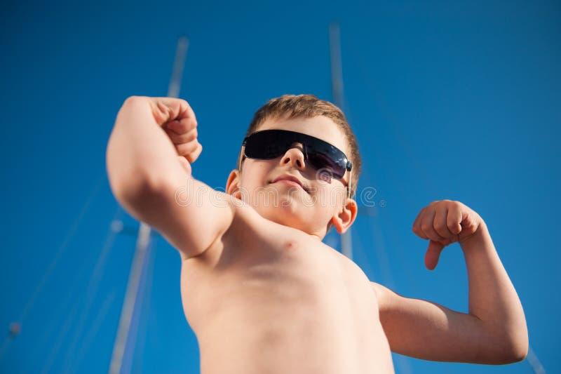Un chico deportivo fuerte con gafas de sol demuestra su gran músculo al aire libre día de verano fotografía de archivo