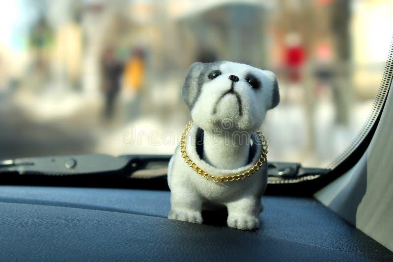 Un chien de jouet de inclination de tête sur le tableau de bord d'une voiture sur un backgrou de fenêtre photographie stock