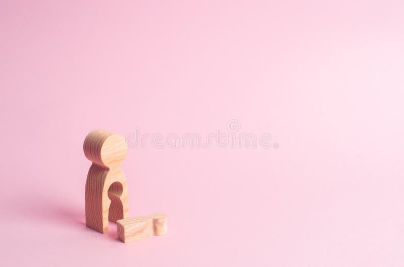 Un chiffre en bois d'une femme avec un vide duquel un enfant est tombé Le concept de la perte d'un enfant, avortement de grossess photographie stock libre de droits