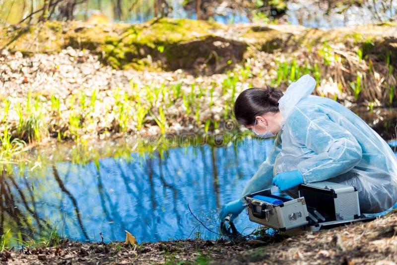 un chimiste entreprend une étude de l'eau d'une source naturelle dans la forêt photos stock