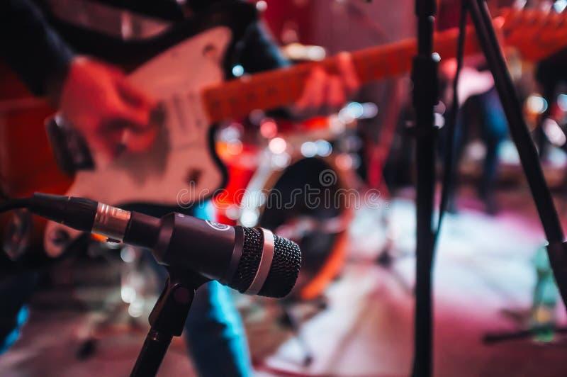 Un chitarrista con il microfono sulla fase immagine stock libera da diritti
