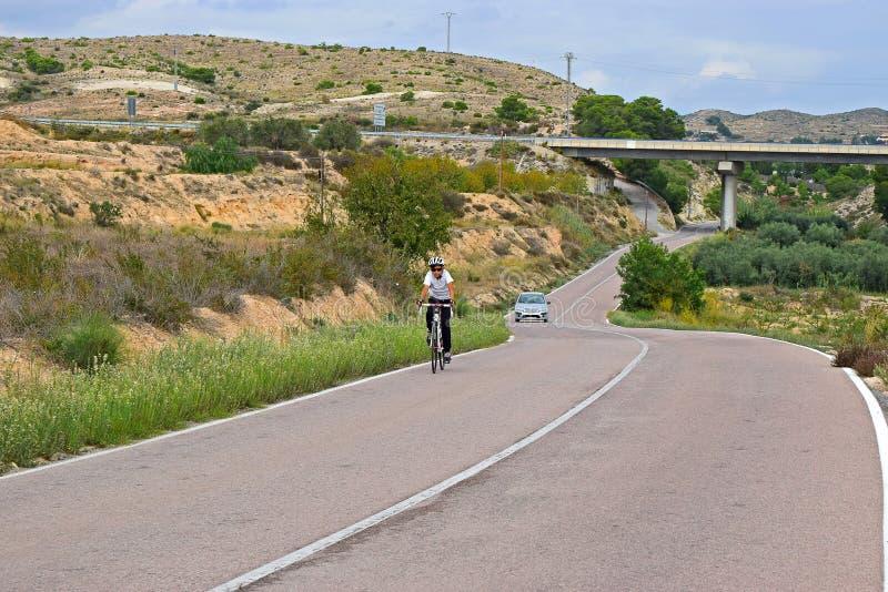 Un ciclista che guida su una collina nel paesaggio sbalorditivo fotografie stock