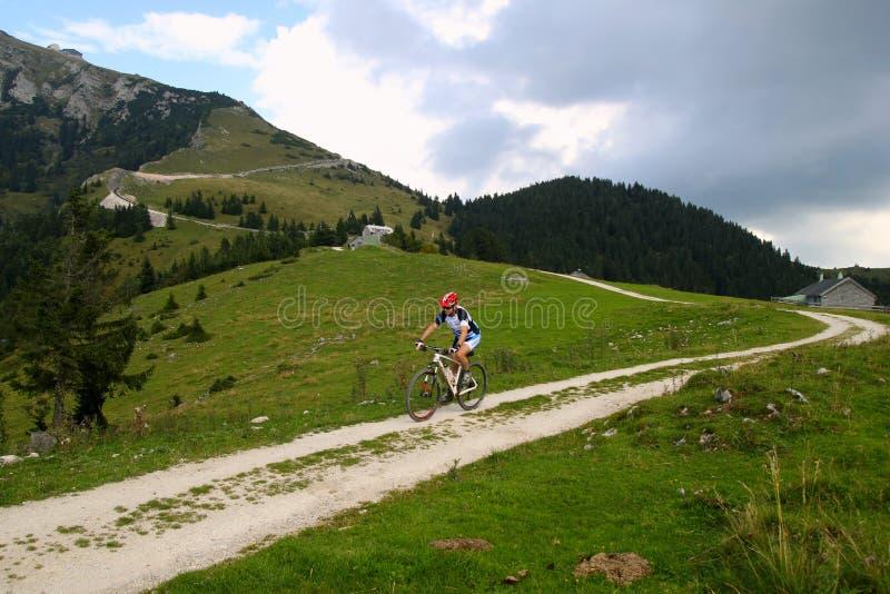 Un ciclista en el camino entre los campos con la opinión sobre las montañas y las casas en las nubes fotos de archivo libres de regalías