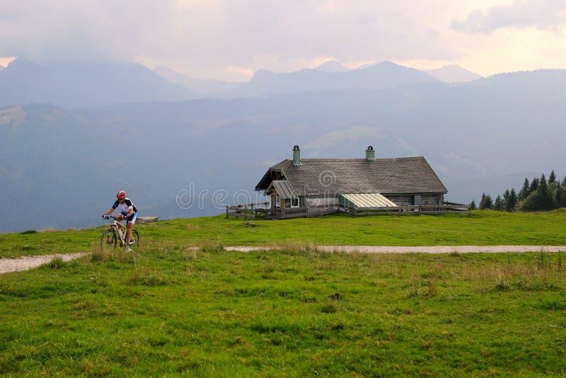 Un ciclista en el camino entre los campos con la opinión sobre las montañas y una casa en las nubes fotografía de archivo libre de regalías