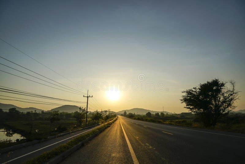 Un ciel bleu et un lever de soleil clairs le long de la longue route photos libres de droits