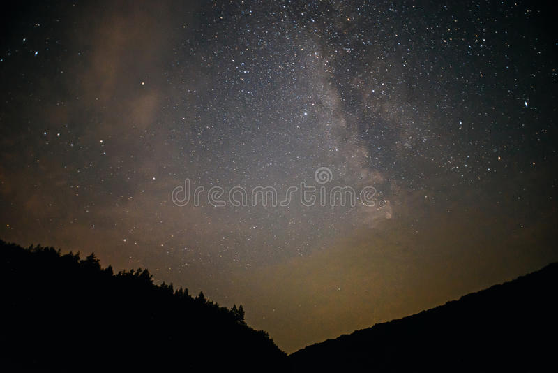 Un ciel nocturne clair avec une colline et arbres dans le premier plan photographie stock libre de droits